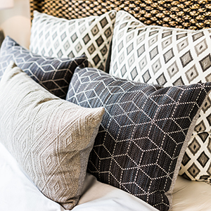 Closeup of new bed comforter with decorative pillows, headboard